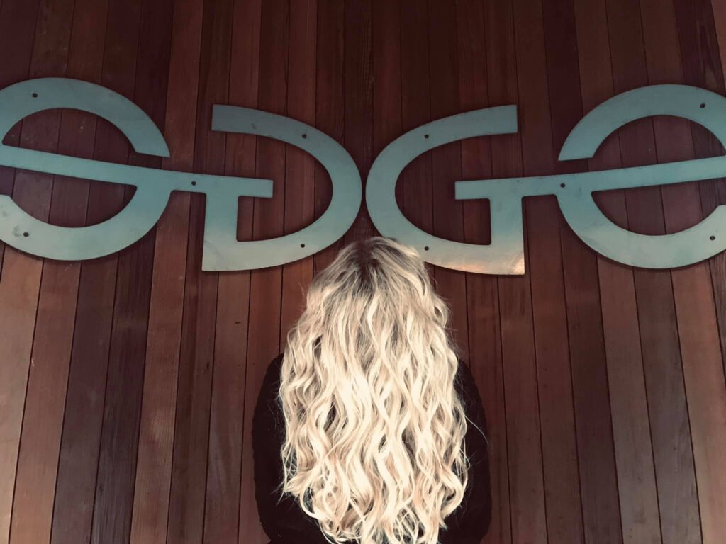 edge salon academy with blonde hair in front of logo on wall